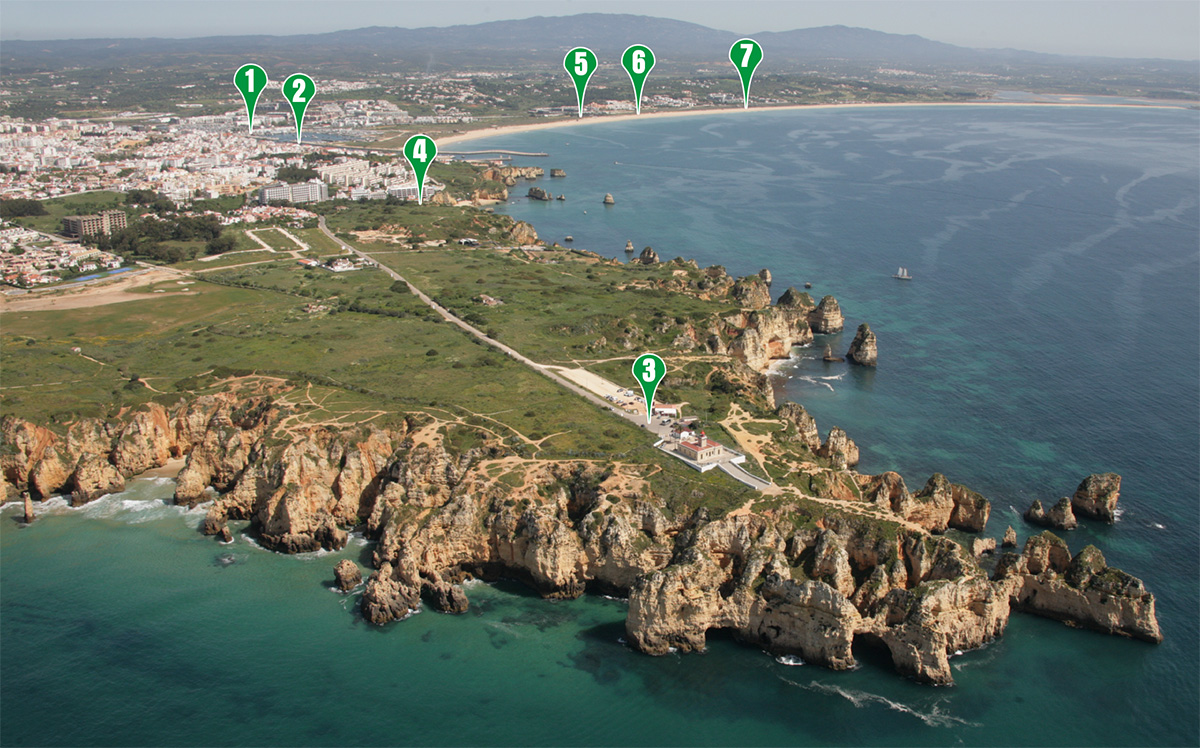 Aerial photograph of Lagos city, Portugal. Contains the number of stops marked for reference on the timetable below. Stop 1: Marina de Lagos (Museu de Cera dos Descobrimentos), Stop 2: Avenida dos Descobrimentos (Direction Ponta da Piedade and D. Ana Beach), Stop 2: Avenida dos Descobrimentos (Direction Marina and Meia Praia), Stop 3: Ponta da Piedade (Grottos / Lighthouse), Stop 4: Praia da D. Ana (Hotel Carvi Beach), Stop 5: Meia Praia (Hotel Vila Galé / Duna Beach), Stop 6: Meia Praia (Aparthotel D. Pedro), Stop 7: Meia Praia (Hotel Sensimar)